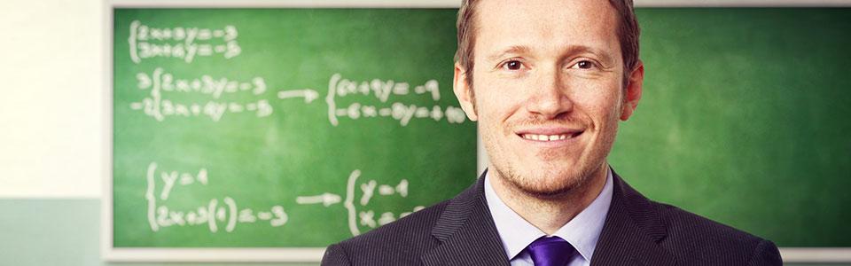 male school superintendent in front of chalkboard